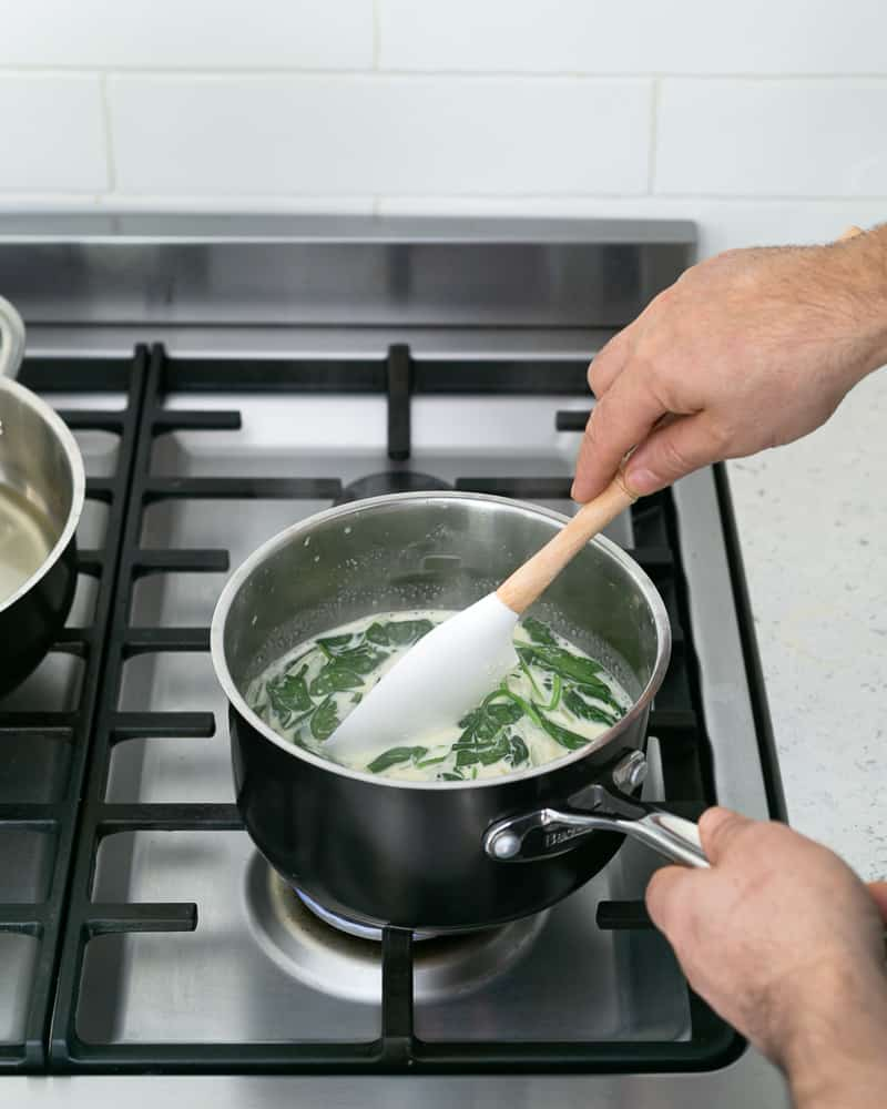 Fresh spinach cooking in vegetable cream stock for the spinach sauce