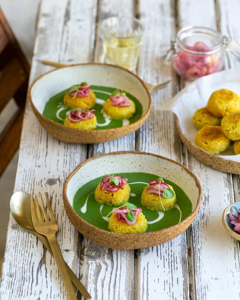 Paneer and Potato Dumplings with Spinach sauce served on a white wooden table