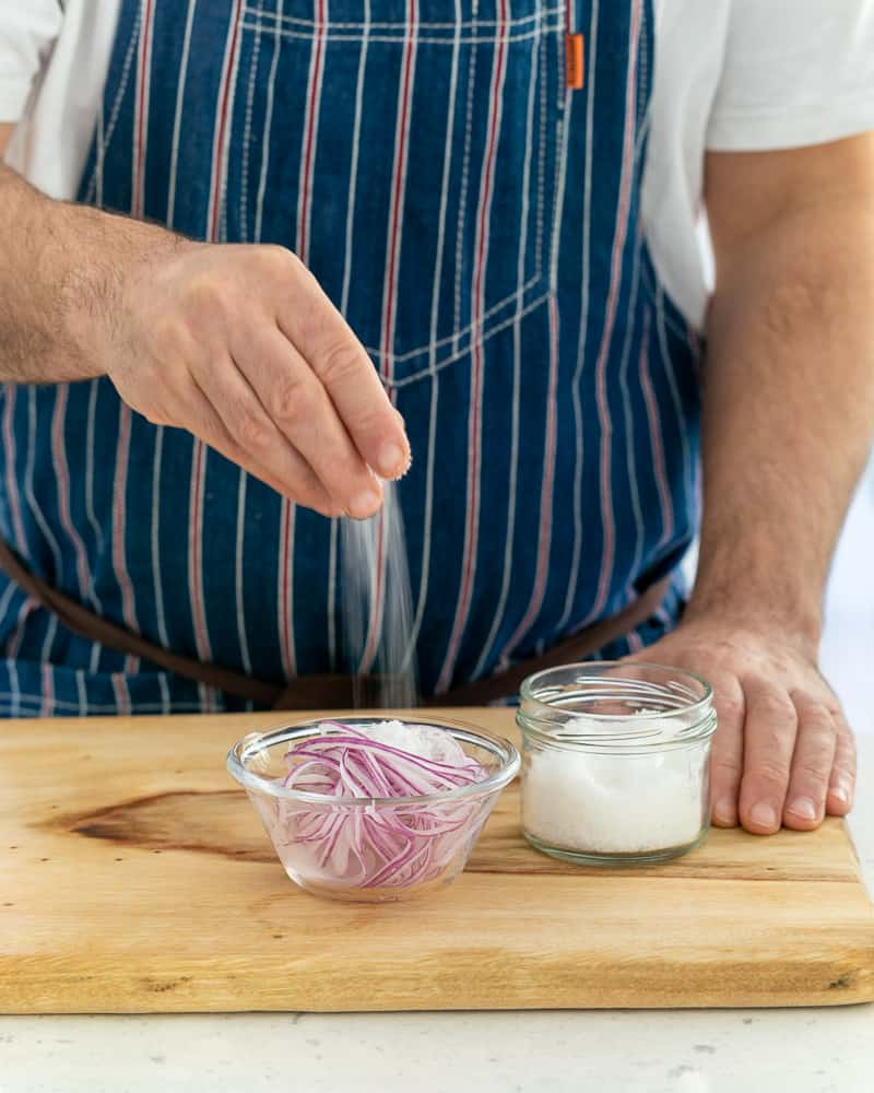 Adding salt to sliced onions to make pickled red onions for garnish