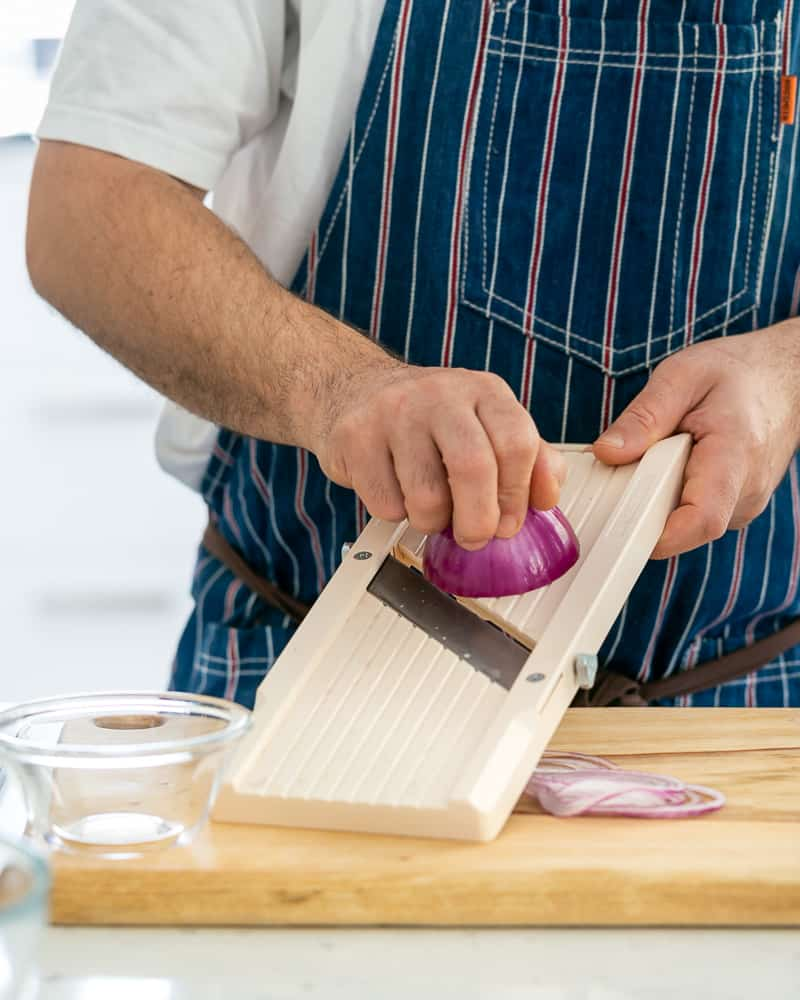 A person slicing red onions to be used as garnish on paneer and potato dumplings with spinach sauce