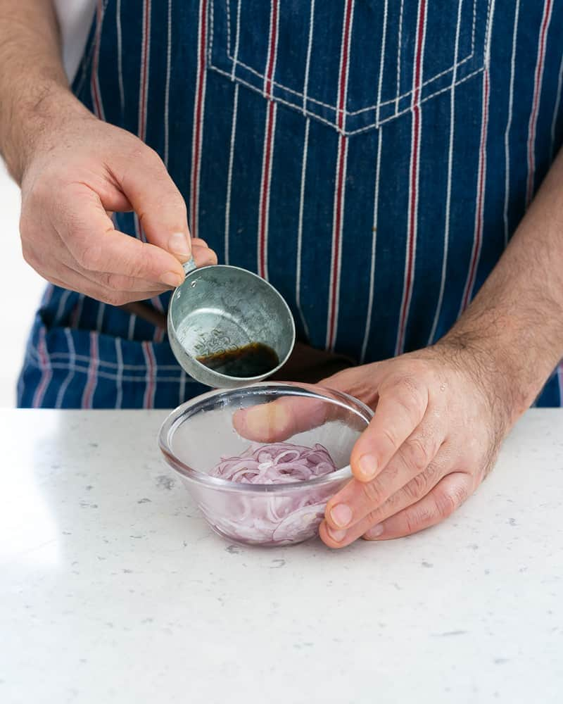 Red wine vinegar added to salted sliced onions