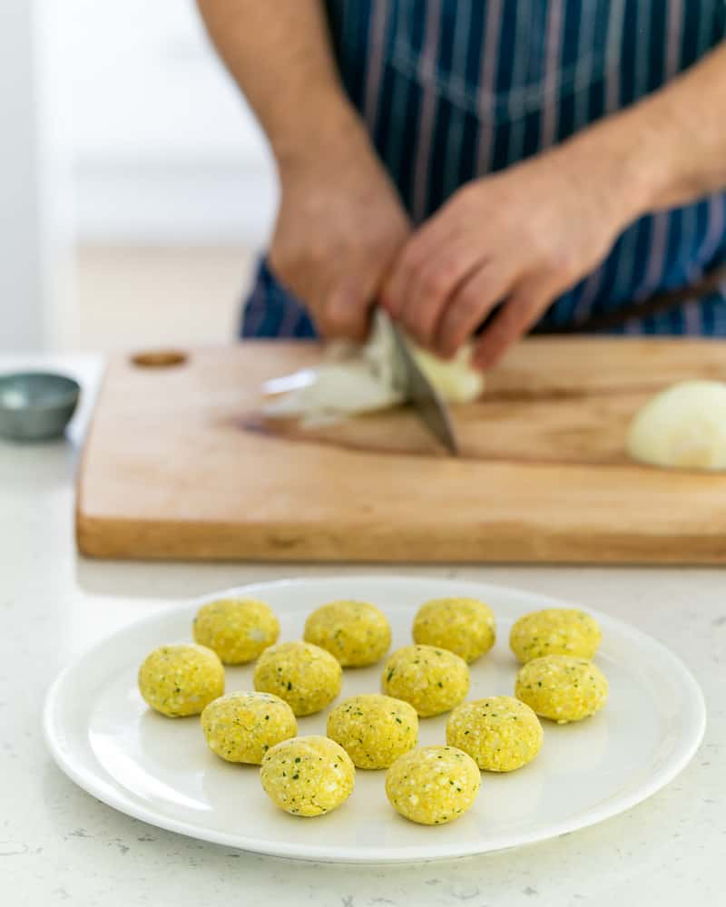 A person slicing onions with the the paneer and potato balls in the front
