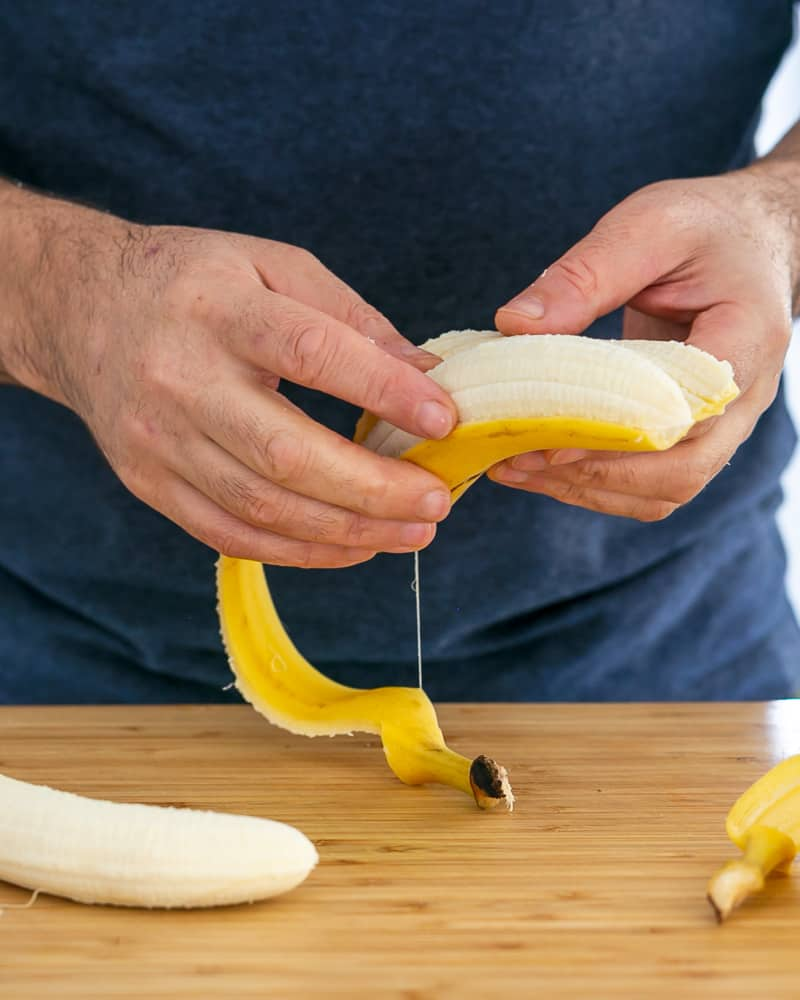 Person peeling banana to caramalize in butter for Dulce de Leche Verrine with Banana and whipped Cream