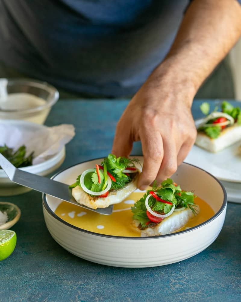 using a spatula turned fish fillets placed on the coconut curry sauce in bowl