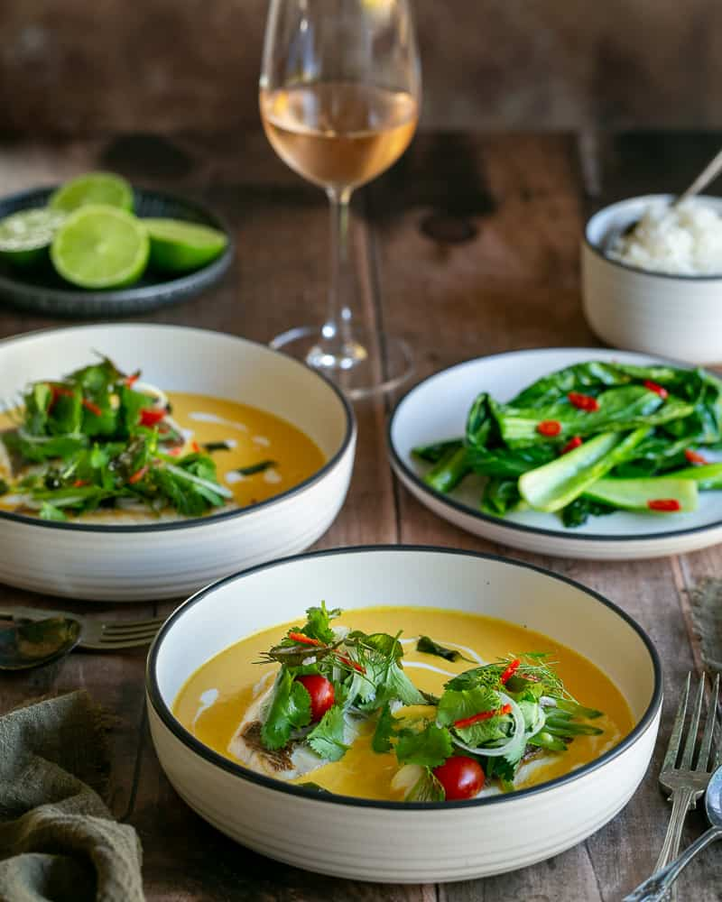 Seared red snapper with coconut curry sauce served in deep white bowls with rice and green vegetables on the side