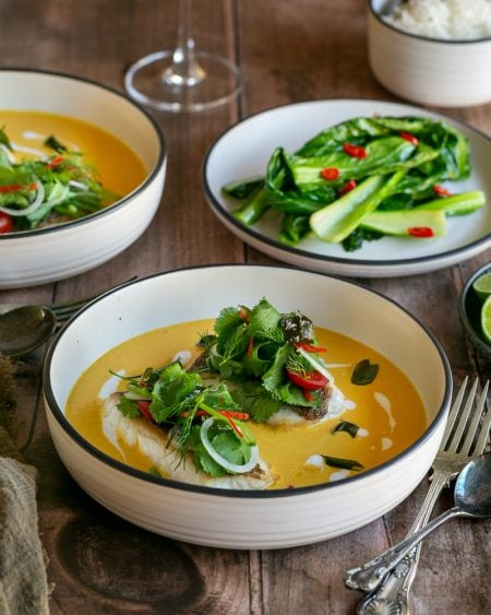 Red snapper with coconut curry sauce served in a deep white bowl garnished fresh herbs