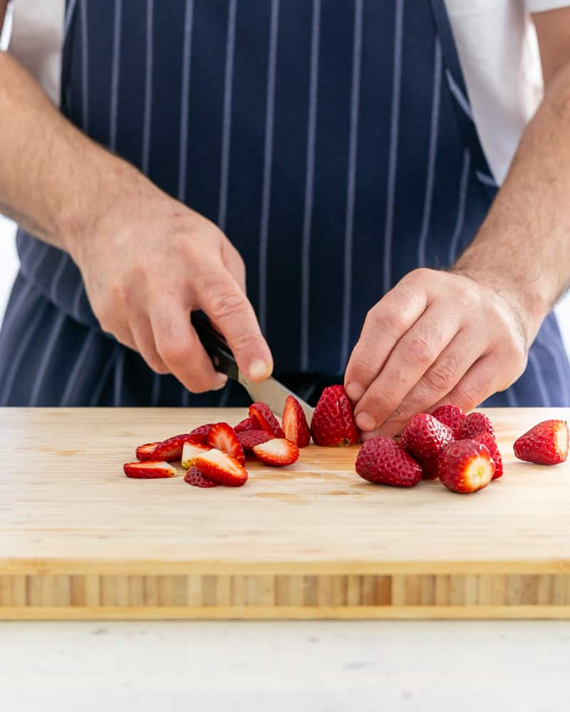Slicing strawberries for Poached Rhubarb with Strawberries and Coconut Chantilly