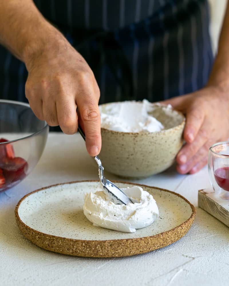 Spreading a spoonful of whipped coconut cream on a plate