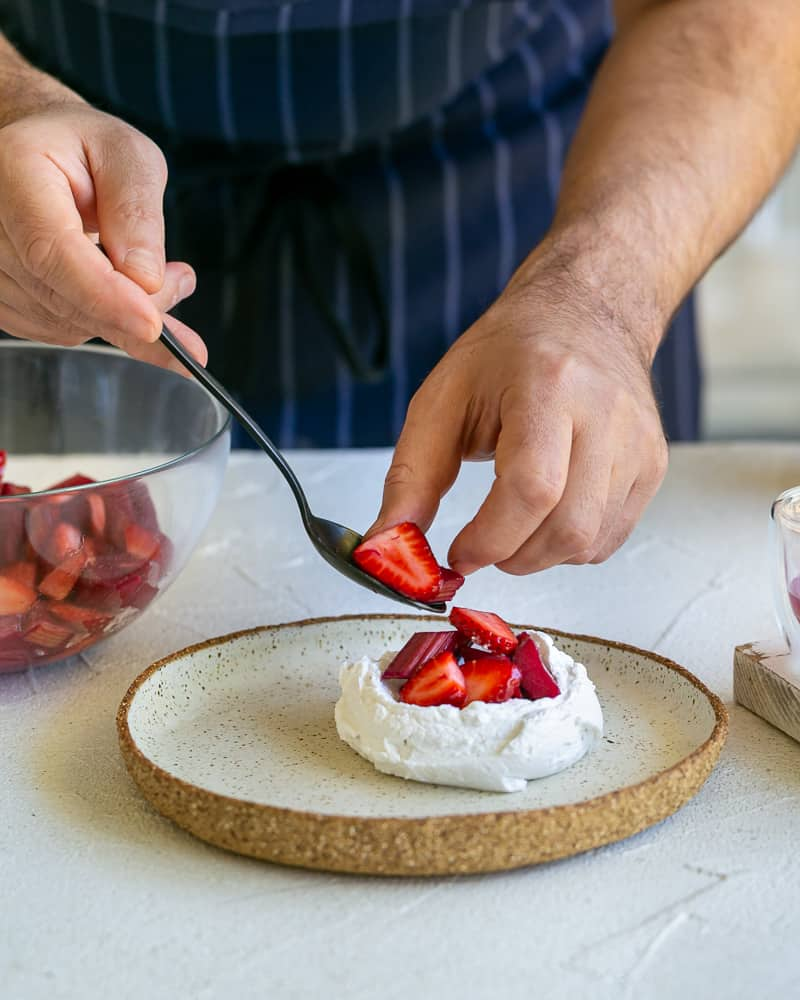 Placing spoonful strawberries and rhubarb on the whipped cream in the plate