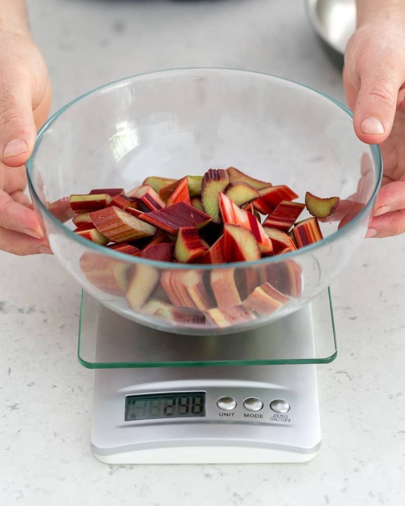 Weighing cut rhubarb in a bowl over a weighing scale