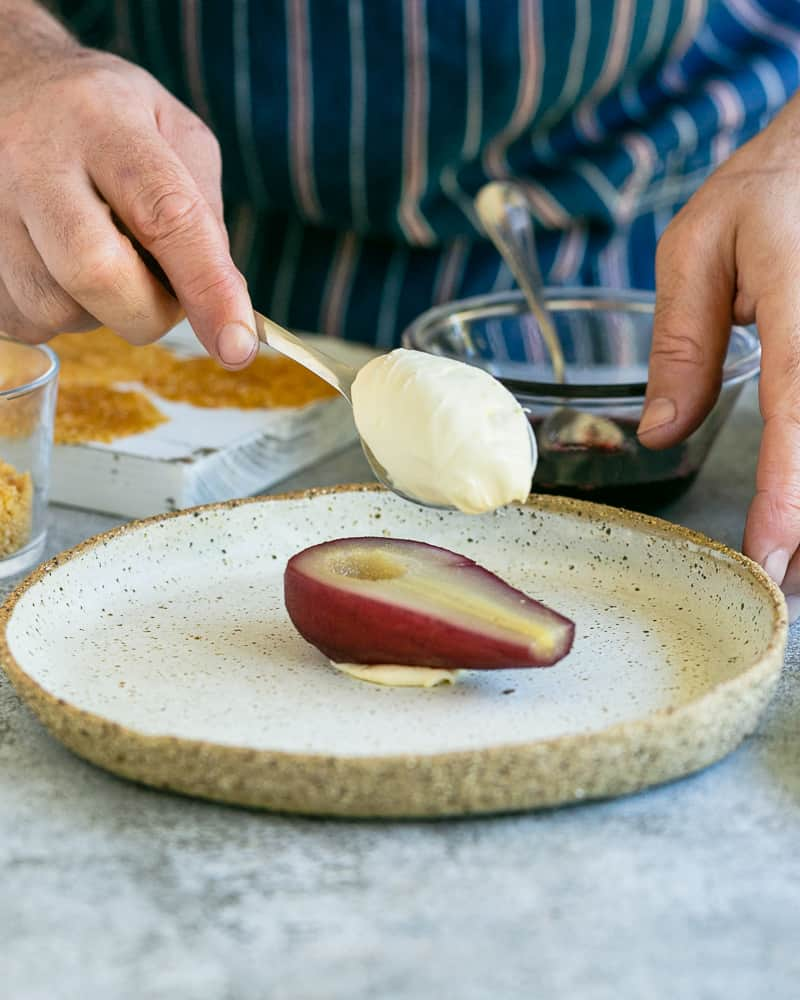 Spoonful of mascarpone on half a pear to assemble Spice poached pears with mascarpone