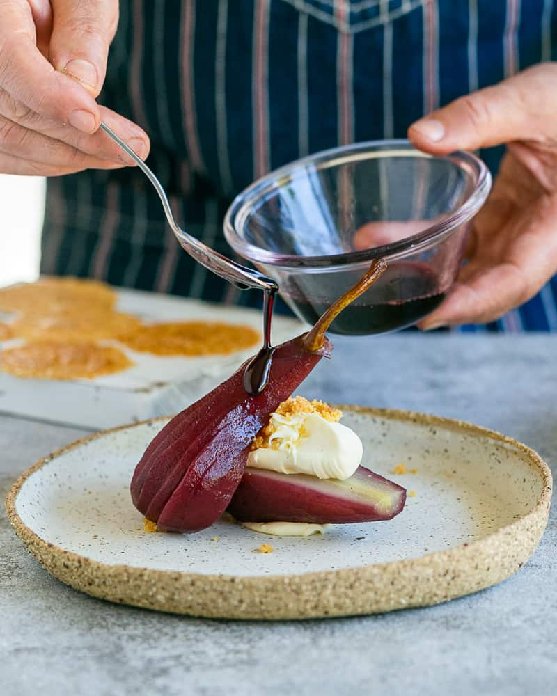 Pouring the wine syrup over the poached pears with the mascarpone and nut brittle