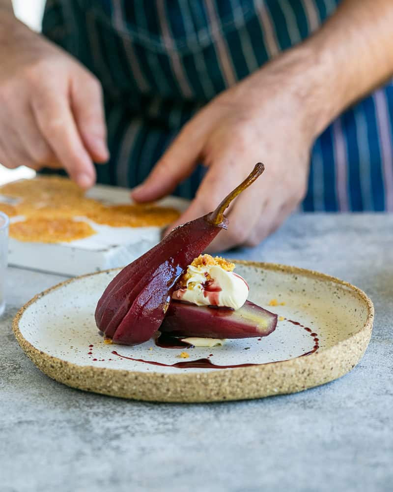 Spiced Poached pears with mascarpone plated in a ceramic plate