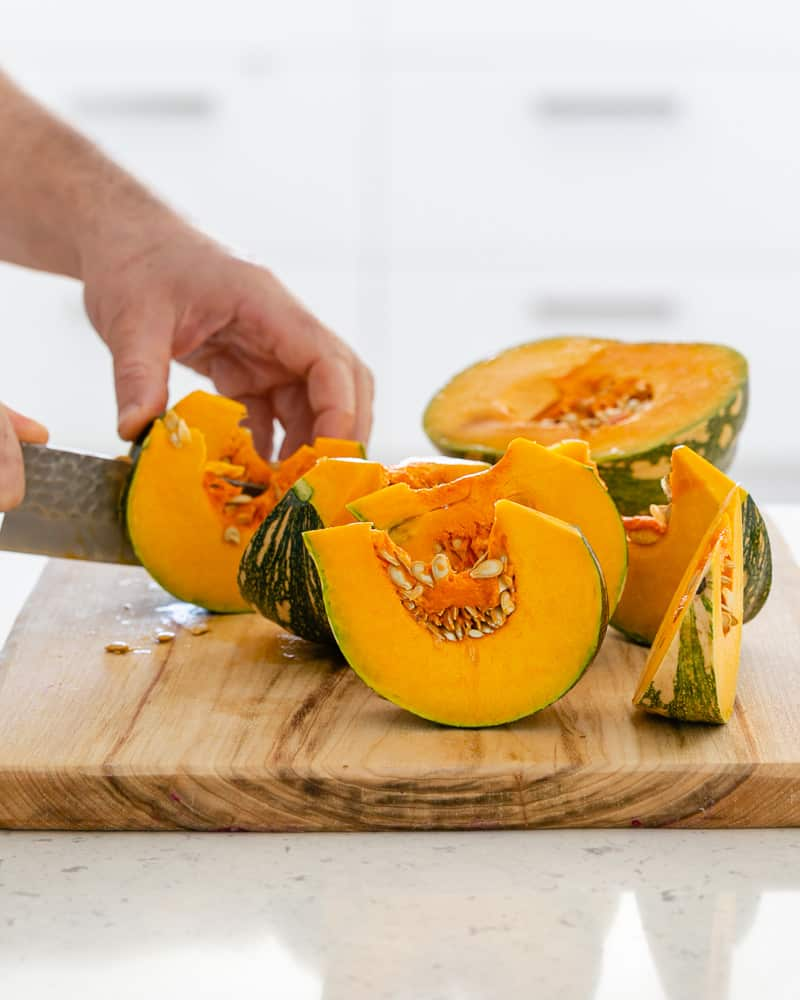 Cutting the pumpkin half into 8 slices