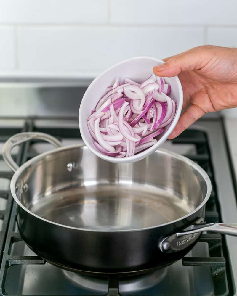 Sliced onions ready to be seared in a hot pan for making coconut curry sauce