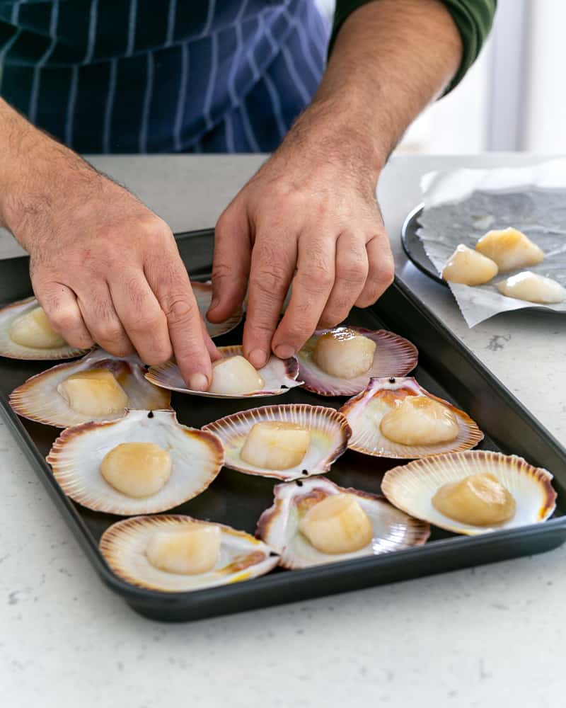 Arranging scallops in their shells on a baking tray