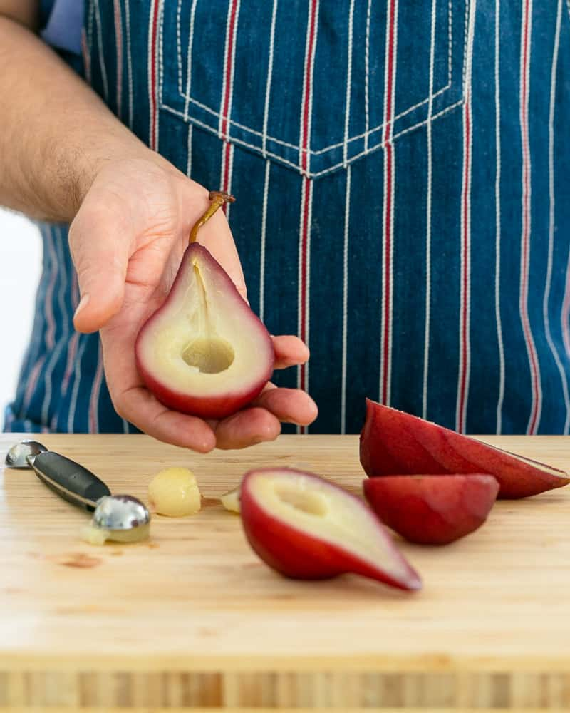 Scooping the centre of a poached pear for assembling Spiced poached pears with mascarpone