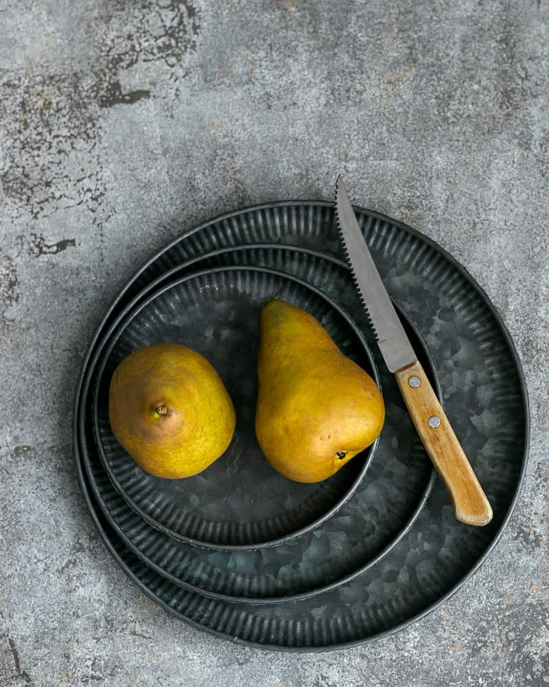 Two Pears on three galvanized plates and a knife