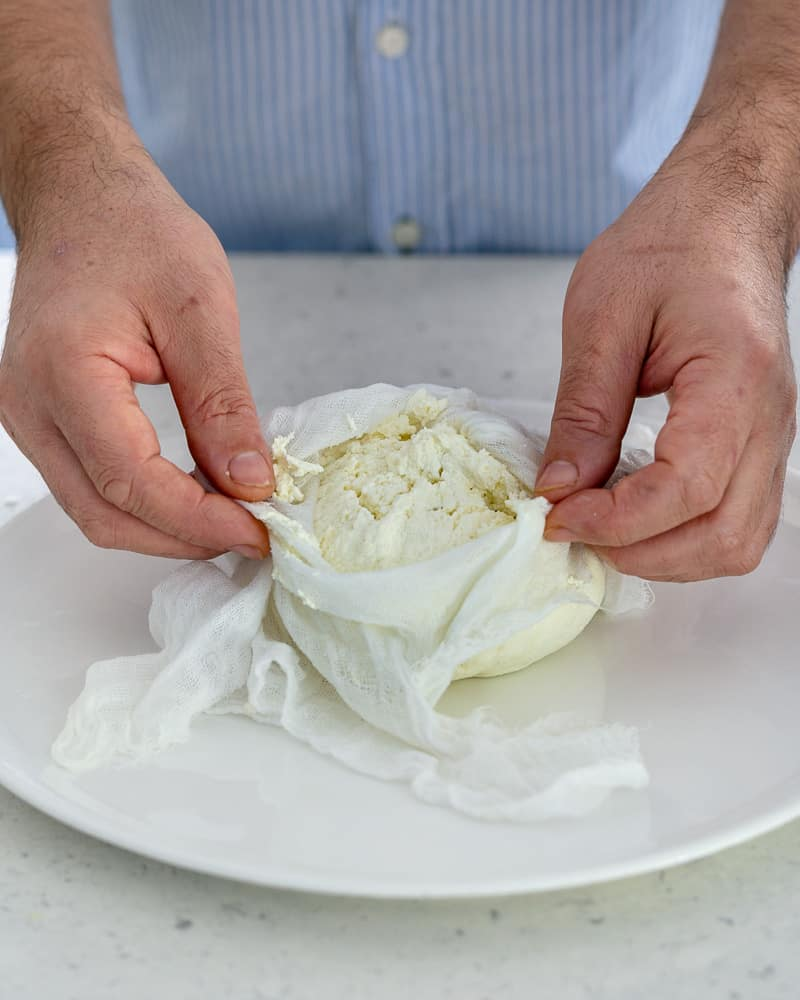 Showing how the cheese in the muslin cloth should look like after draining out the whey to make paneer