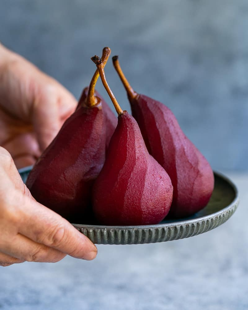 Four poached pears in red wine on a metal plate