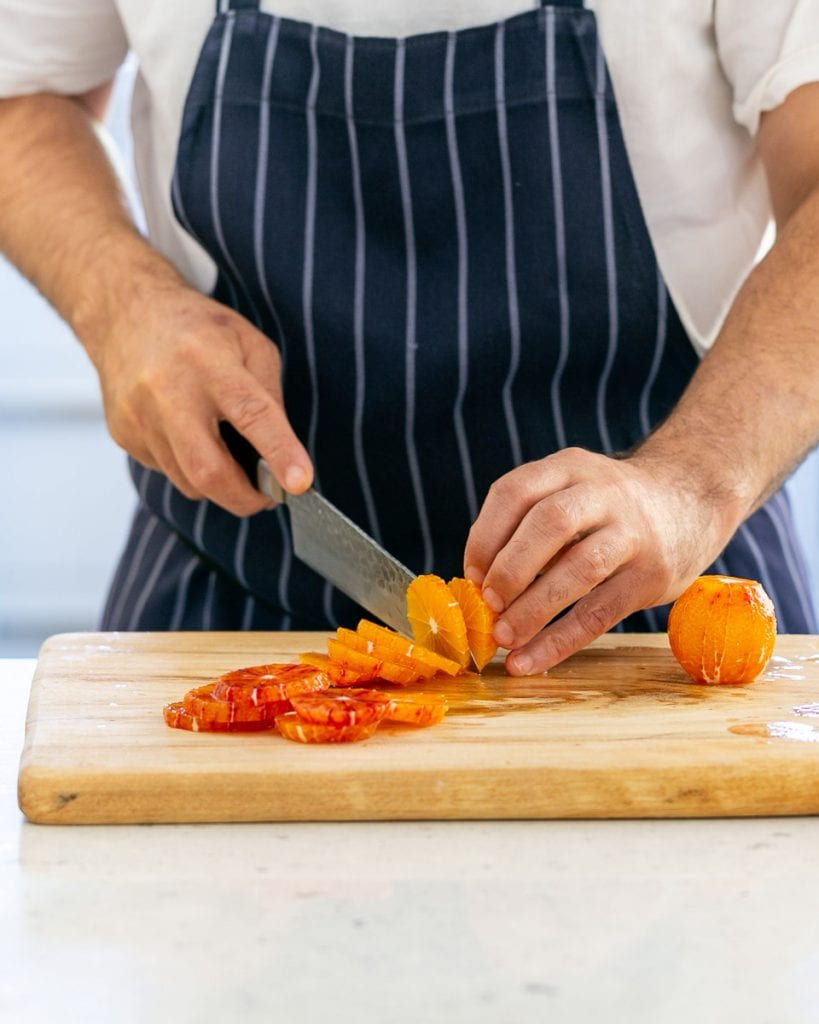 Cutting blood orange rounds with a knife
