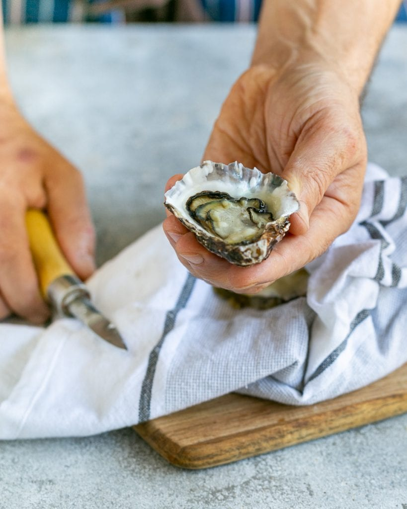 Shucking raw oysters with an oyster knife