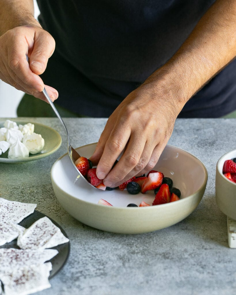 Arranging the mixed berries in a bowl