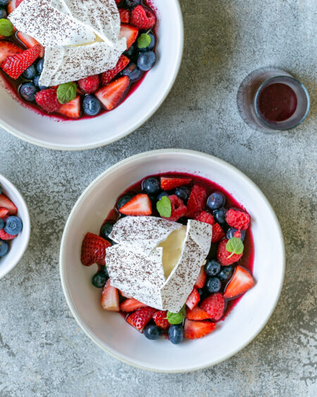 White chocolate mousse with mixed berries and meringue served in a bowl