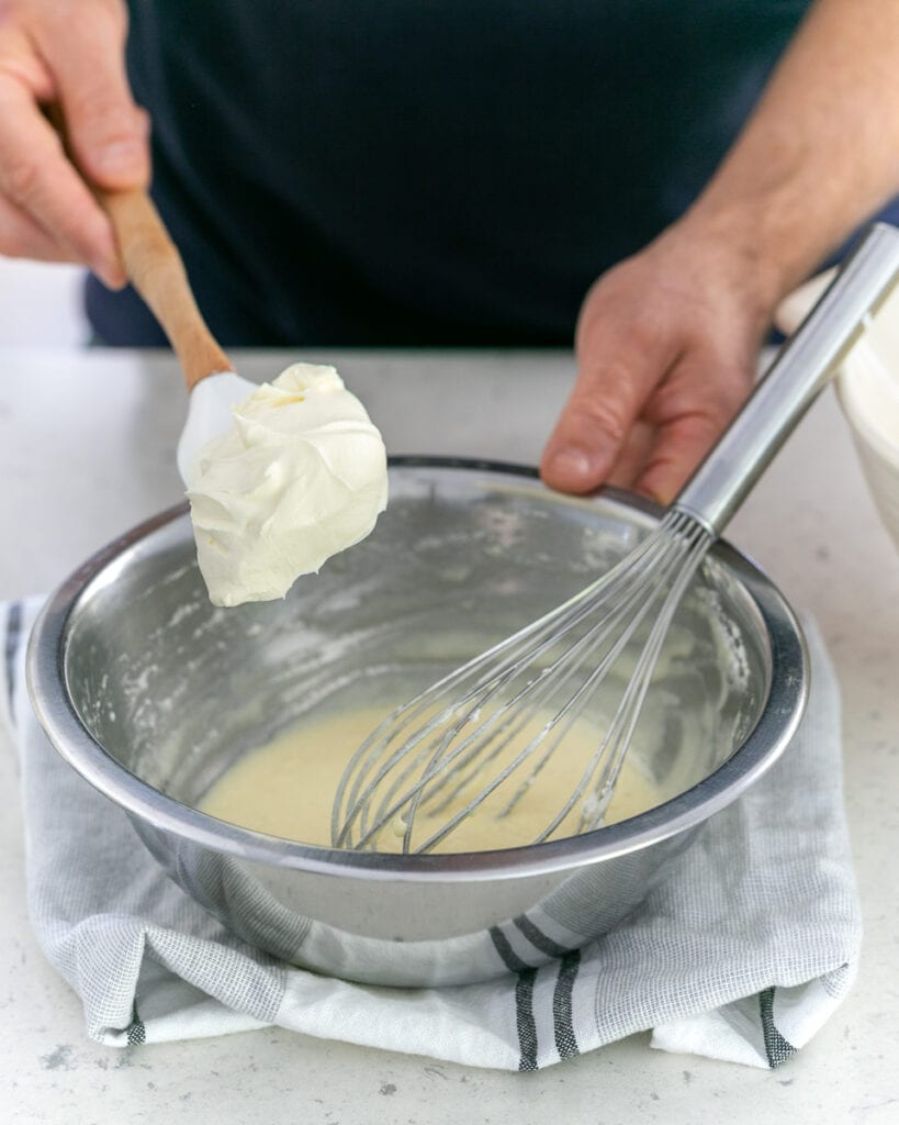 Adding whipped cream to melted chocolate and egg white mix